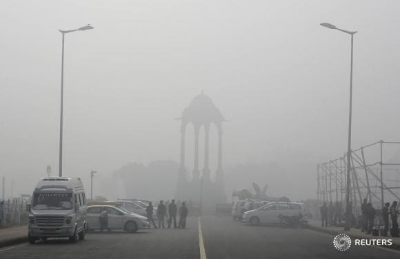 Vendors selling drinks stand beside vehicles near the India Gate war memorial on a smoggy day in New Delhi